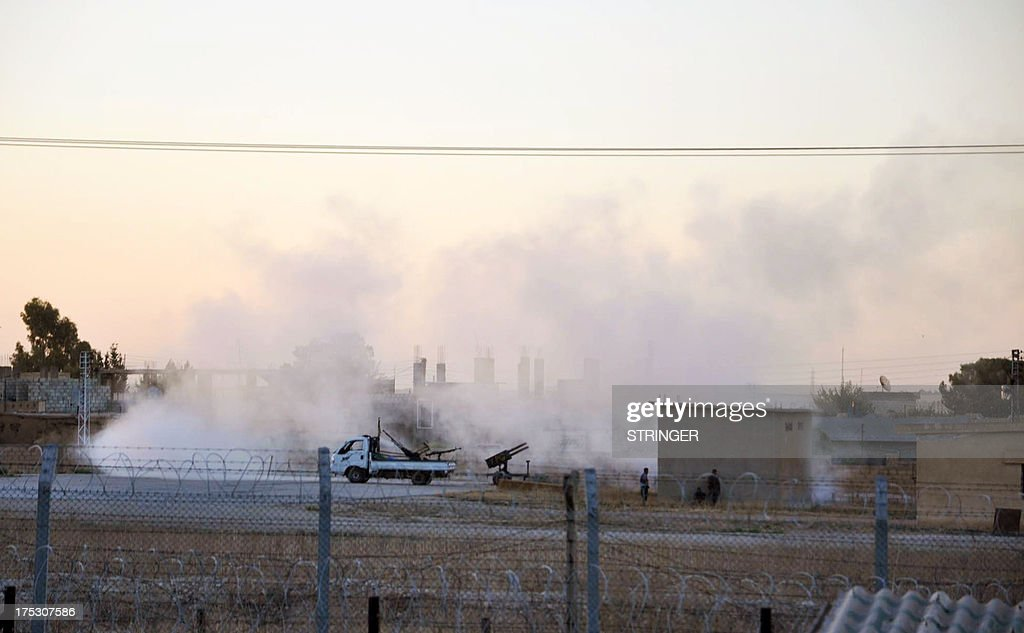 Kurdish fighters are pictured from the Turkish town Ceylanpinar as they stand near a rocket launcher on August 2, 2013 during clashes between the Syrian jihadist group Al-Nusra Front and the Syrian Democratic Union Party (PYD) in the border Syrian town of Ras al-Ain.
