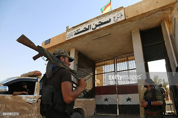 Kurdish fighters belonging to the police force the Asayesh and the People's Protection Units stand outside the central prison in the northeastern...