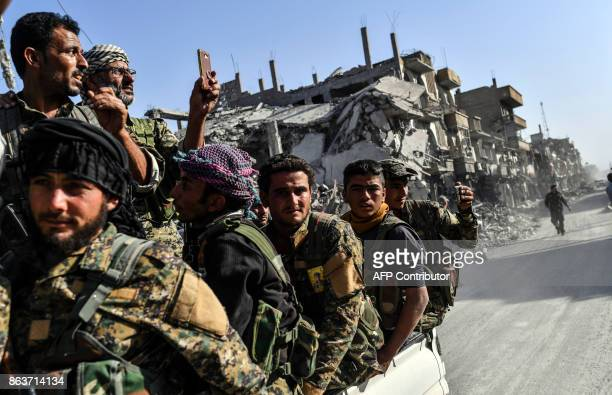 Kurdish fighters of the Syrian Democratic Forces ride in the back of a truck passing damaged buildings in Raqa on October 20 after a Kurdishled force...