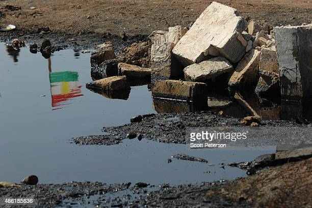 Kurdish flag at a peshmerga checkpoint is reflected in pools of oil with damaged oil pipeline infrastructure as Iraqi Kurdish forces push the...