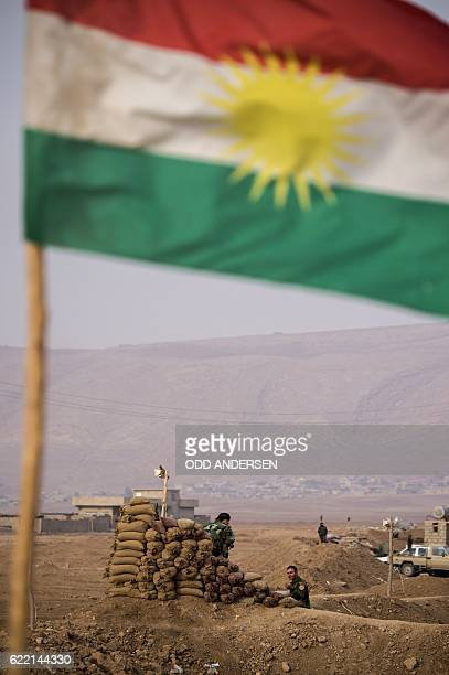 A Kurdish flag flutters as Peshmerga forces guard their position on a sand berm north of the Iraqi Kurdish checkpoint village of Shaqouli some 35...