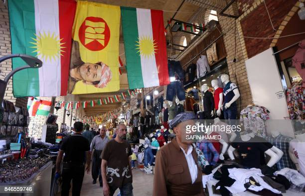 Kurdish flags and a flag bearing the portrait of the president of Iraq's Kurdistan region hang above stalls near the citadel in Arbil the capital of...