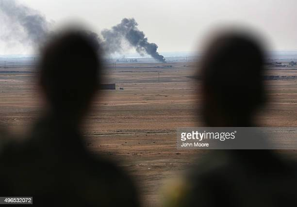 Kurdish forces overlook a burning oil well on November 10 2015 near the ISILheld town of Hole Rojava Syria Troops from the Syrian Democratic Forces a...