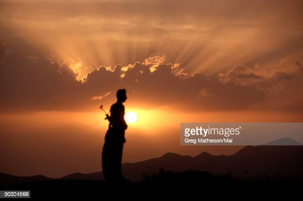 Kurdish freedom fighter, a memberof PUK , standing atop mountain as sun sets on protective area of Northern Iraq.