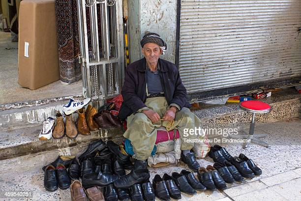CONTENT] A kurdish Iraqi street vendor wearing traditional baggy trousers selling shoes in the old covered market of Sulaymaniyah Iraqi Kurdistan...