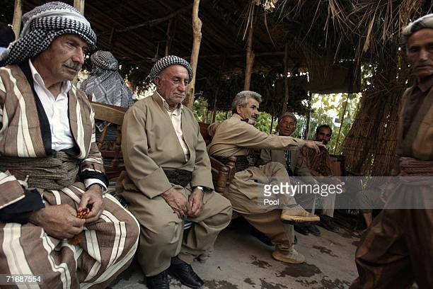 Kurdish Iraqis gather at a cafe to watch the broadcast of the first day of ousted Iraqi President Saddam Hussein's trial over the Anfal campaign of...