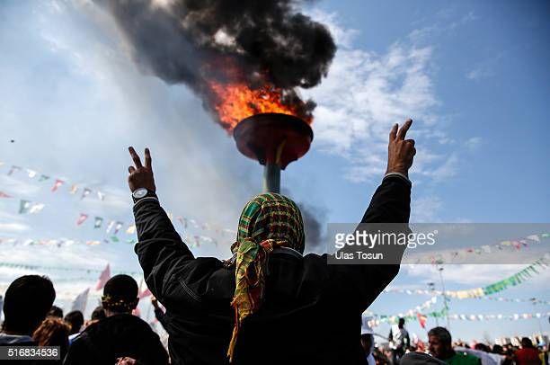 Kurdish man flashes vsigns during Newroz celebrations on March 21 2015 in Diyarbakir Turkey Thousands of Kurds gather for the Newroz spring festival...