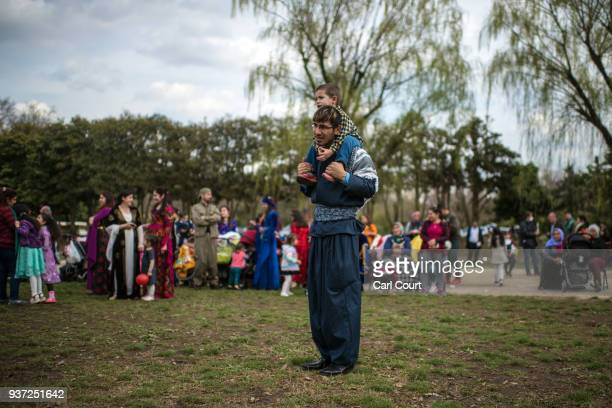 Kurdish man in traditional attire carries a child on his shoulders as he looks on during Nowruz celebrations on March 24 2018 in Tokyo Japan Nowruz...
