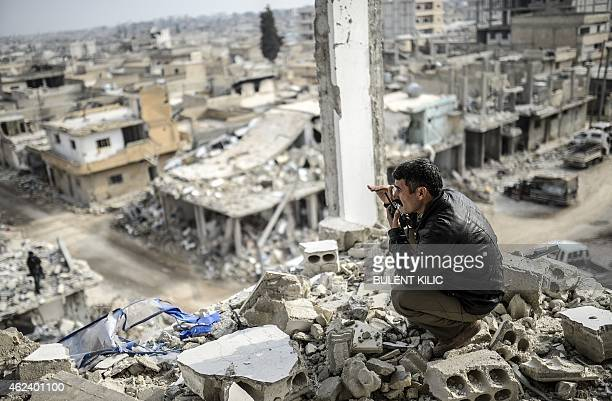Kurdish man talks with a radio as he checks the eastern part of the Syrian border town of Kobane, known as Ain al-Arab, on January 28, 2015. Kurdish...
