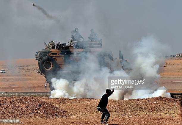 Kurdish man throws stones at a Turkish armoured vehicle firing tear gas as Turkish army soldiers try to remove people from the Turkish-Syrian border...
