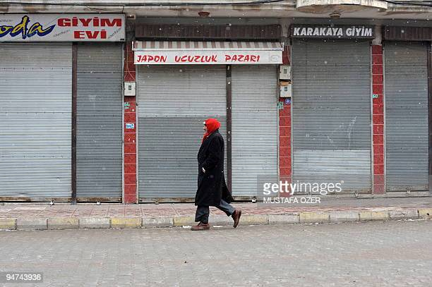 A Kurdish man walks in front of the closed shops in the town of Bulanik Mus province on December 16 shop owners shut their businesses to protest...