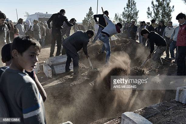 Kurdish men bury the coffin during the funeral of a Kurdish People's Protection Units fighter in Suruc, Turkish southeastern Sanliurfa province, on...