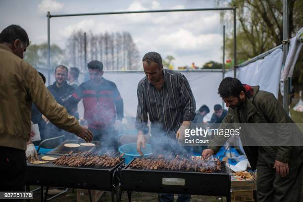 Kurdish men grill kebabs at snack stand during Nowruz celebrations on March 24 2018 in Tokyo Japan Nowruz meaning 'new day' and marking the first day...