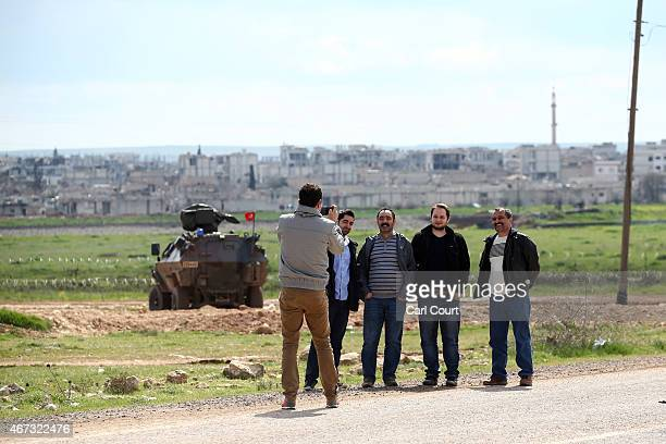 Kurdish men have their photo taken with the ruined Syrian town of Kobani in the background on March 22, 2015 in Suruc, in the province of Sanliurfa,...