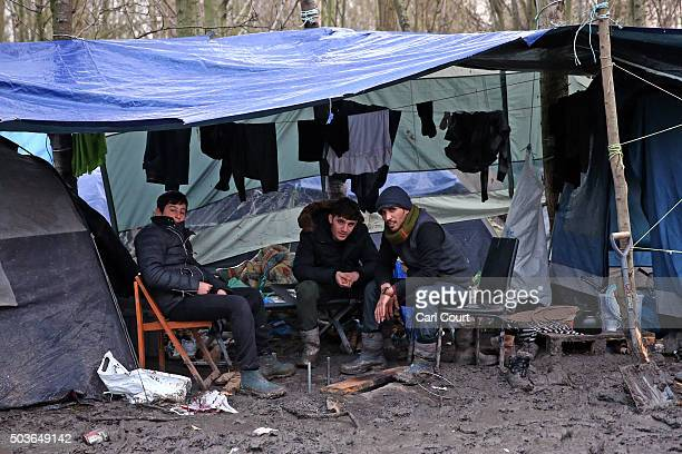 Kurdish men rest under a shelter in a new migrant camp on January 6 2016 in Dunkirk France Thousands of migrants continue to live in makeshift camps...