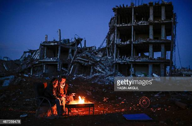 Kurdish men sit near bonfire near a destroyed building, in the Syrian Kurdish town of Kobane, also known as Ain al-Arab, on March 22, 2015. AFP...