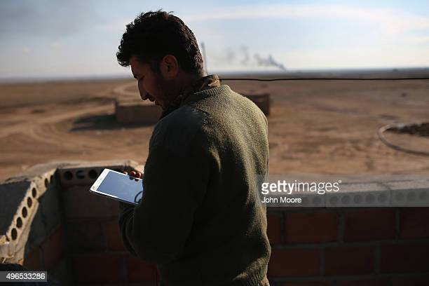 Kurdish officer from the Syrian Democratic Forces coordinates frontline troop movements with the aid of a tablet at a forward operating base on...