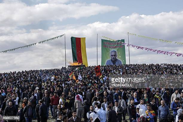 Kurdish people gather near a Kurdish flag and banner bearing a portrait of jailed Kurdish leader Abdullah Ocalan as they celebrate Newroz which marks...