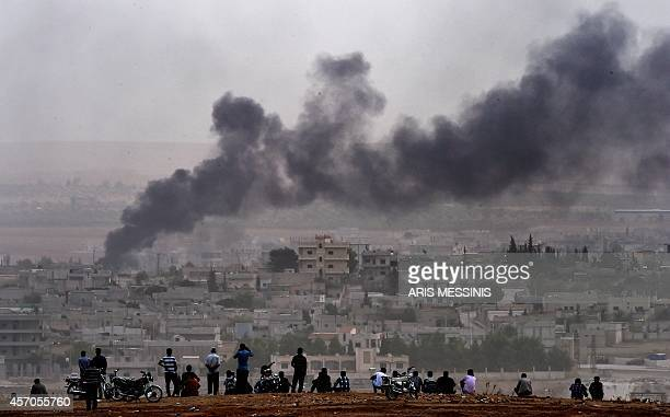 Kurdish people look at smoke rising from the Syrian town of Ain al-Arab, known as Kobane by the Kurds, from the Turkish-Syrian border, on October 11,...