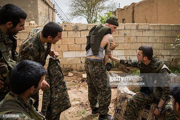 Kurdish People Protection Unit fighters look at a tattoo of a 26year old from the US nicknamed by Kurdish fighters as Hewal Dilsad on April 16 in the...