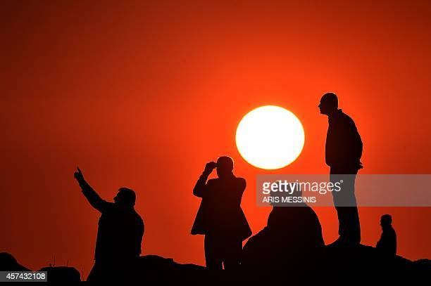 Kurdish people watch the Syrian town of Kobane also known as Ain alArab from the Turkish border in the southeastern village of Mursitpinar Sanliurfa...