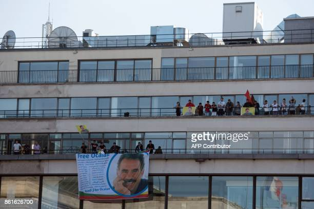Kurdish people wave flags and banners picturing jailed Kurdish leader Abdullah Ocalan as they take part in a demonstration on the balconies after...