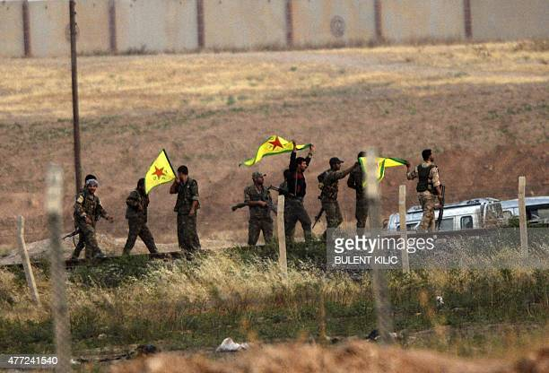 Kurdish People's Protection Units fighters hold their movement's flag near the Akcakale crossing gate between Turkey and Syria at Akcakale in...