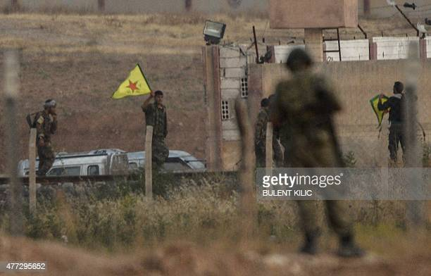 Kurdish People's Protection Units fighters hold their movement's flag while a Turkish soldier looks at them near the Akcakale crossing gate between...