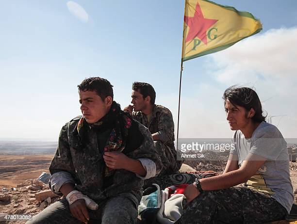 A Kurdish People's Protection Units or YPG fighters stand near a check point in the outskirts of the destroyed Syrian town of Kobane also known as...