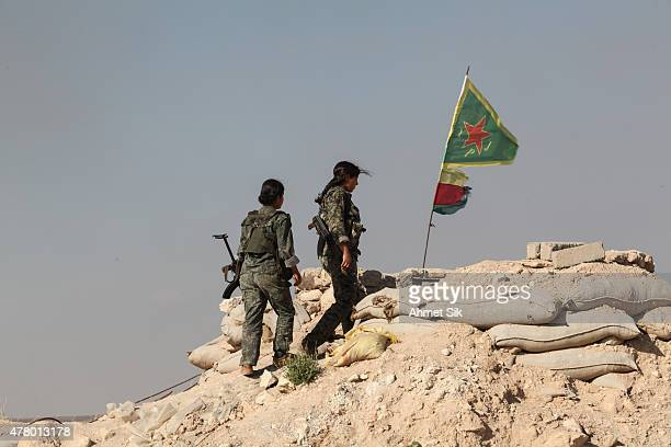 Kurdish People's Protection Units or YPG women fighters walk to reach a check point in the outskirts of the destroyed Syrian town of Kobane also...