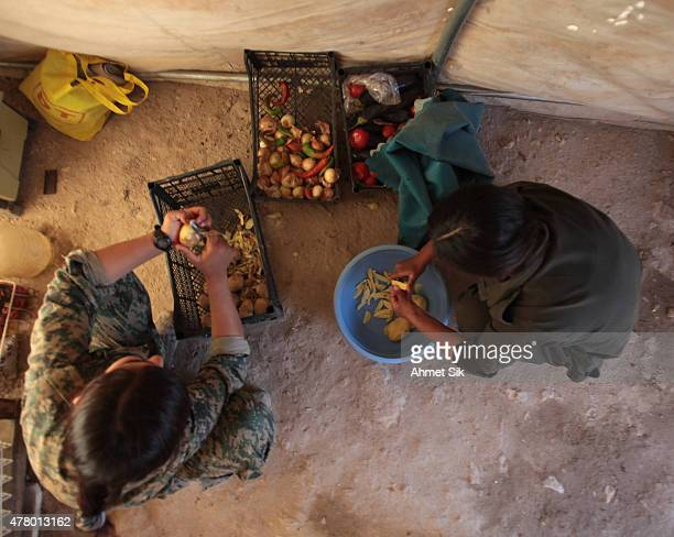 Kurdish People's Protection Units or YPG's women fighters prepares their lunch in a base camp at the outskirts of the destroyed Syrian town of Kobane...
