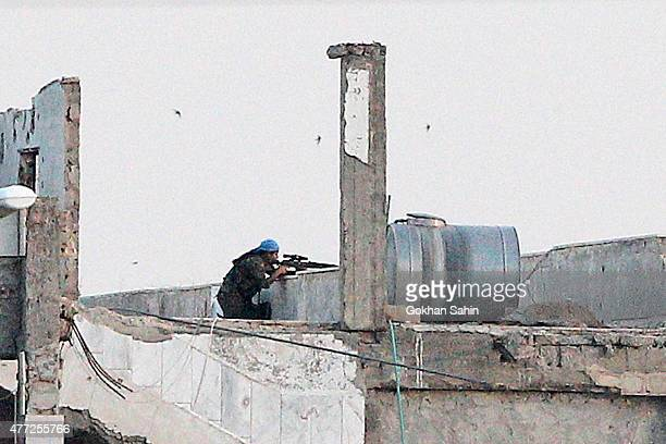 Kurdish People's Protection Units sniper takes position in the northern Syrian town of Tel Abyad as they are pictured from the Turkish border town of...