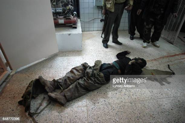 Kurdish Peshmerga and morgue workers kick the head as they carry one of nine Ansar fighters killed in the USKurdish Peshmerga war against Ansar the...