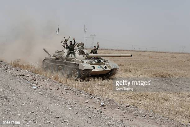 Kurdish Peshmerga drive a tank that was abandoned by the Iraqi army toward Kirkuk in Northern Iraq, near the current front line between ISIS and...