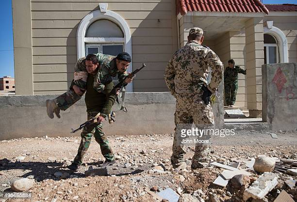 Kurdish Peshmerga fighter carries a comrade during as a German military trainer supervises in the last week of a military training course on November...