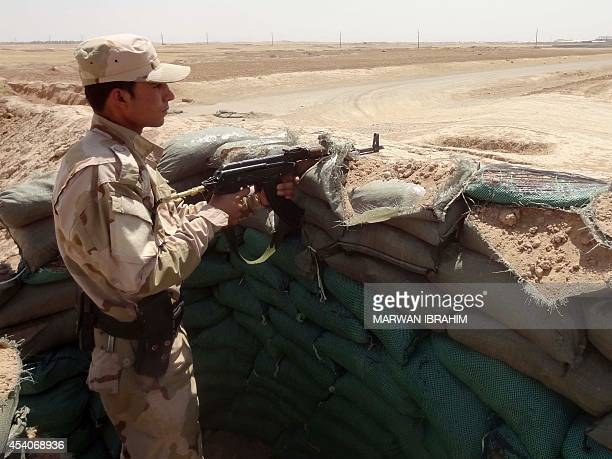 A Kurdish Peshmerga fighter takes a position to monitor security and movements around Kirkuk on August 24 2014 Three nearsimultaneous car bombs...