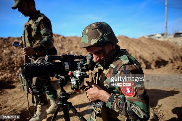Kurdish Peshmerga fighter uses a scope to measure the distance during fighting against Islamic State group on November 8, 2014 in the Syrian besieged...