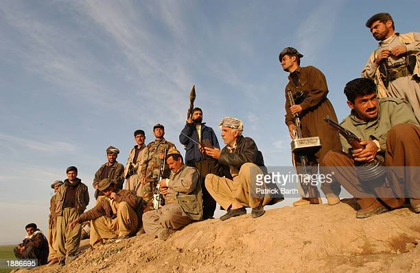 Kurdish Peshmerga fighters follow the news and observe the coalition bombing campaign as they overlook the positions of the Iraqi army, March 30,...
