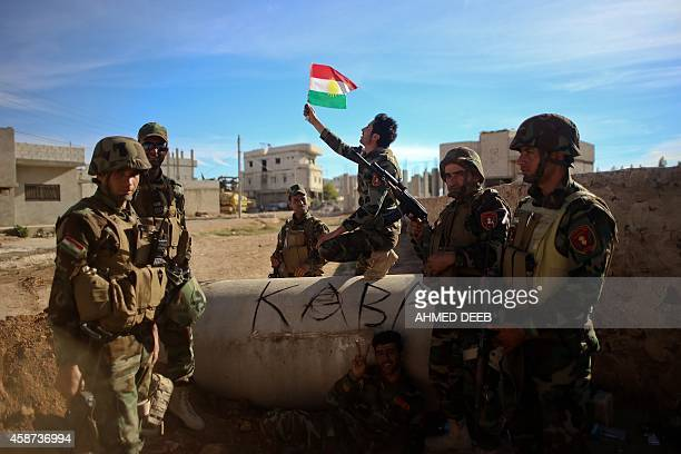 Kurdish Peshmerga fighters pose for a picture during a break in fighting against Islamic State group on November 8 2014 in the Syrian besieged border...