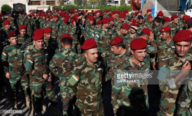 Kurdish Peshmerga fighters queue up outside a polling station in Arbil before voting for parliamentary election in Iraq's autonomous Kurdish region...