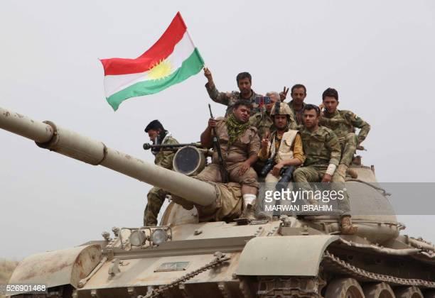 Kurdish Peshmerga fighters sit on top of a tank waving the Kurdish flag on the front line some 35 kilometres south of Kirkuk after they recaptured...