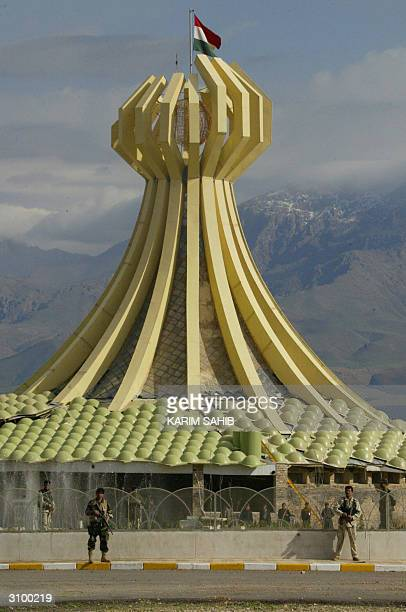 Kurdish peshmerga fighters stand guard 16 March 2004 outside a memorial site built for the victims of the 1988 Halabja massacre in the center of the...