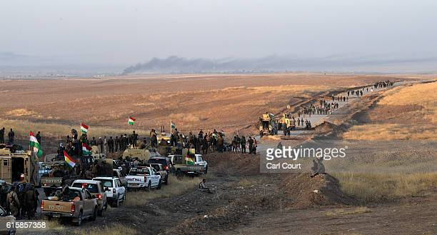 Kurdish peshmerga forces move forward from an assembly point as they prepare to begin an assault to recapture the village of Tiskharab from ISIS on...