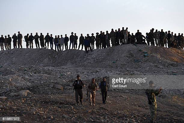 Kurdish peshmerga forces move forward from an assembly point as they prepare to recapture the village of Tiskharab from ISIS on October 20, 2016 near...