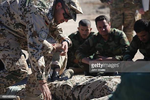Kurdish Peshmerga forces watch as a German doctor teaches battlefield first aid during a medical training session on November 3 2015 in Erbil Iraq...