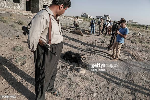 Kurdish Peshmerga look at the body of an alleged Islamic State fighter who was killed during an American airstrike outside of the town of Gwar in...