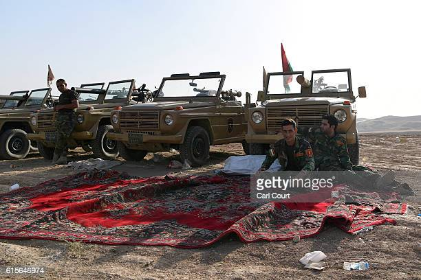 Kurdish peshmerga military vehicles are parked as soldiers relax near a road to Mosul as forces continue the battle to retake Mosul on October 19...