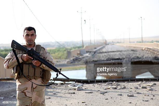 Kurdish peshmerga patrol of a bridge leading from Guver village to Mosul, destroyed by army groups led by Islamic State , formerly known as ISIL, on...