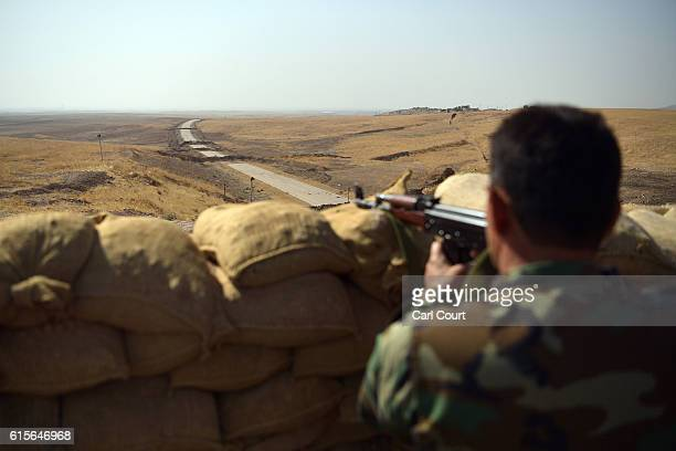 Kurdish peshmerga soldier aims his rifle toward a road to Mosul as forces continue the battle to retake Mosul on October 19 2016 in Bashiqa near...
