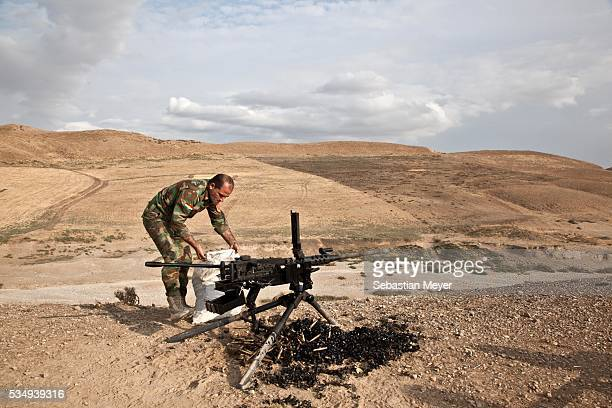 Kurdish peshmerga soldier cleans up shell casings after a training with the British military The British government has equipped the Kurdish...